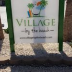 village by the beach sign
